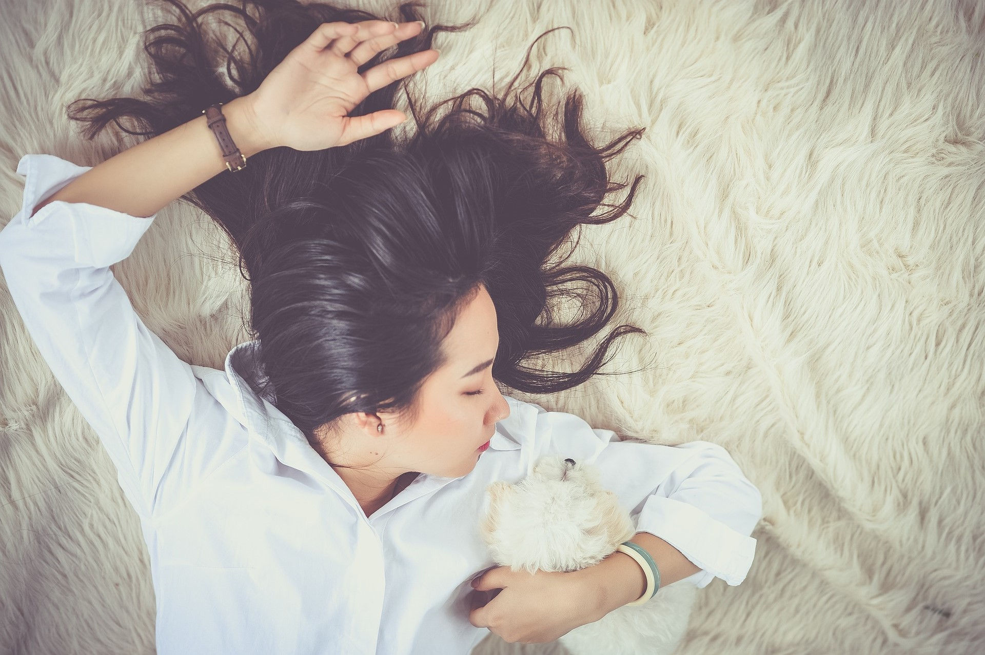 Girl wearing white shirt from boutique sleeping with puppy